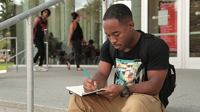 Man sitting on steps, intently writing into a journal.